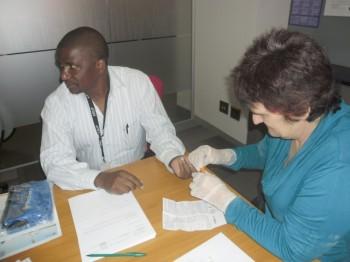 Community Mobiliser Silvia doing a PSA test on a male employee